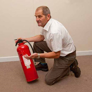 Image of a man holding a Fire Extinguisher